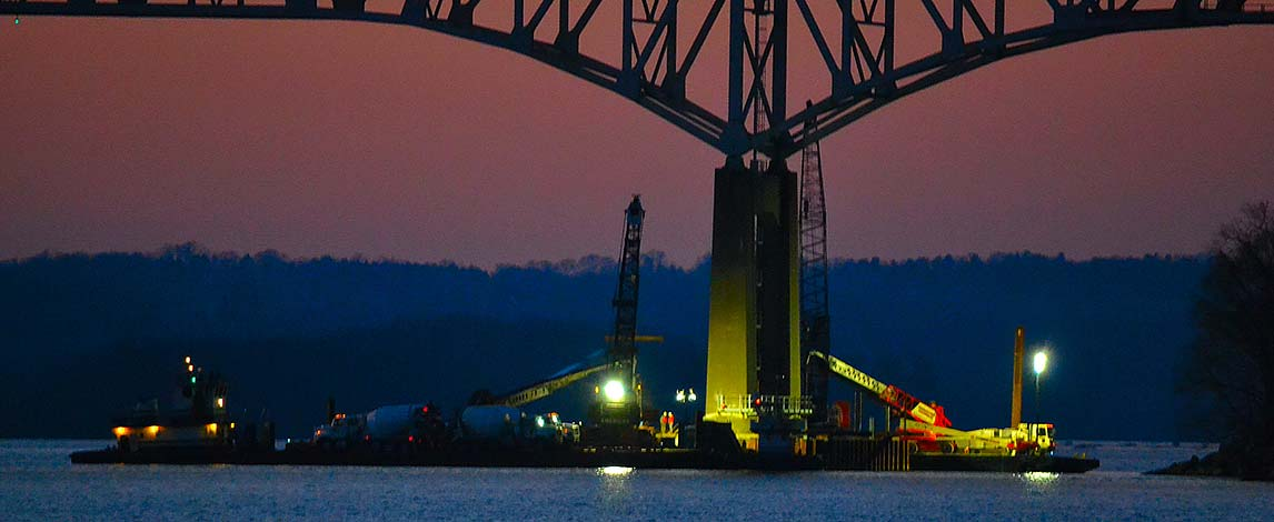 concrete pumping under Susquehanna River bridge at night